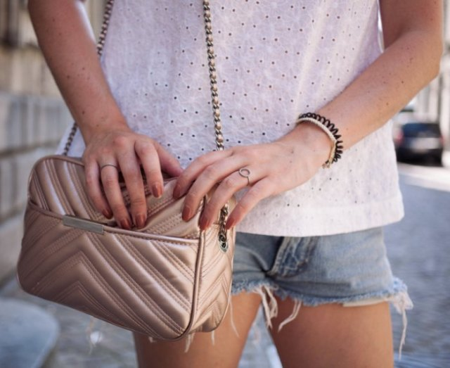 white blouse with blue denim shorts and rose gold purse
