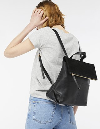 gray t-shirt with light blue skinny jeans and leather backpack