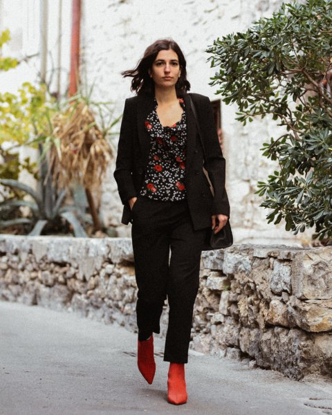 black blazer with printed top with a scoop neckline and brown boots on the boot