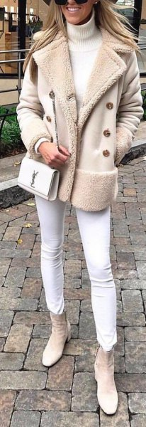 Light pink coat with fleece collar, white jeans and light gray ankle boots with side zip