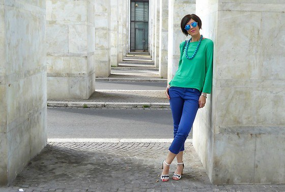 Bright emerald green long-sleeved top with a relaxed fit and short-cut jeans in royal blue