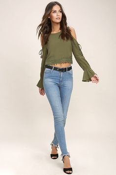 olive green long-sleeved top with a cold shoulder and light blue jeans
