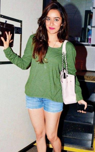 green long-sleeved T-shirt with light blue mini denim shorts