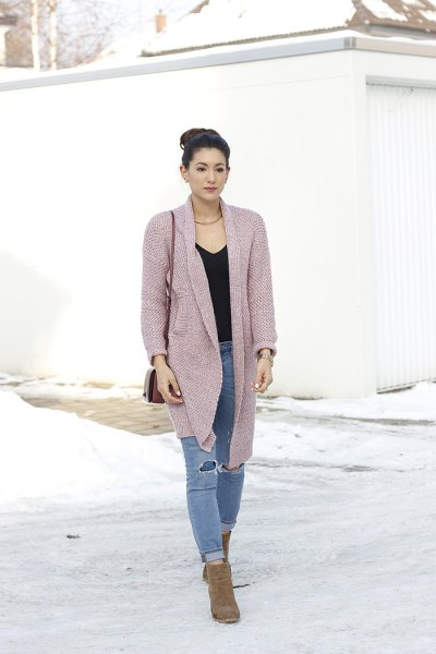 pink cardigan with black V-neck and torn jeans
