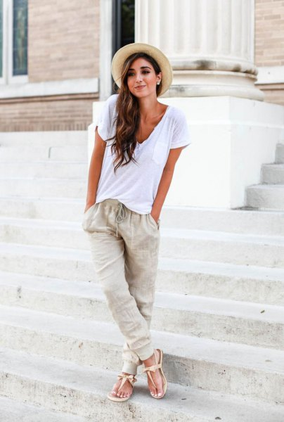 white t-shirt with a deep v-neck, straw hat and jogger linen trousers