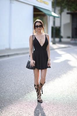 black cocktail dress with deep v-neck and flap with knee-high strappy sandals
