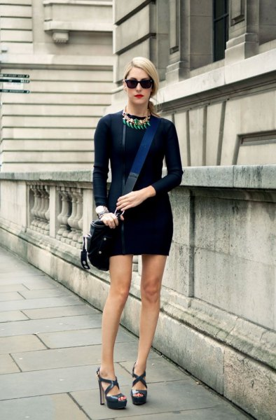 black, long-sleeved, figure-hugging mini dress with dark blue sandals