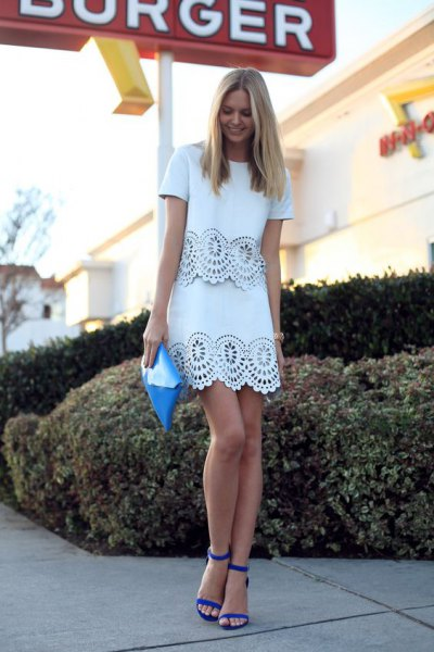 white lace mini dress with serrated edge and blue sandals