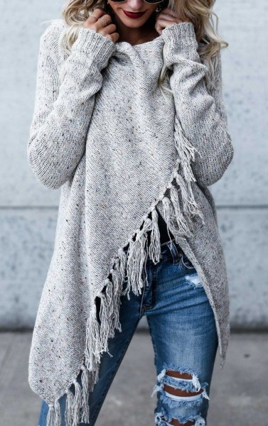 gray wrap sweater with fringes and blue, destroyed jeans