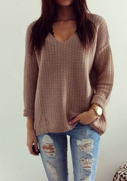 gray knitted sweater with V-neck and relaxed fit with torn boyfriend jeans