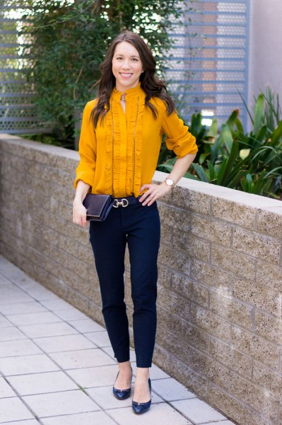 Mustard yellow pleated shirt with buttons and dark blue chinos