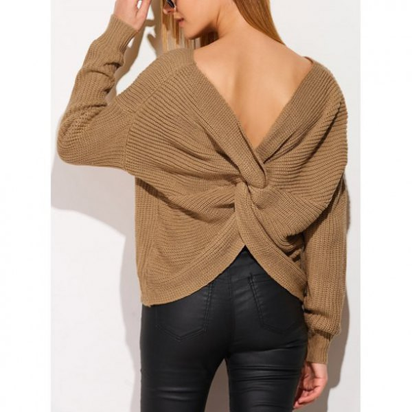 green twist-back sweater with black coated skinny jeans