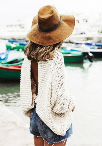 white, oversized long sleeve sweater with blue denim shorts and floppy hat