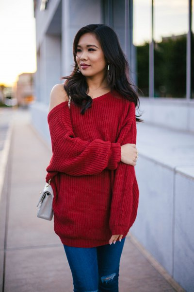 red, chunky tunic sweater with blue jeans