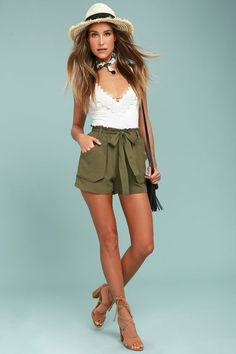 white camisole with a deep V-neck and green shorts with a high tie front
