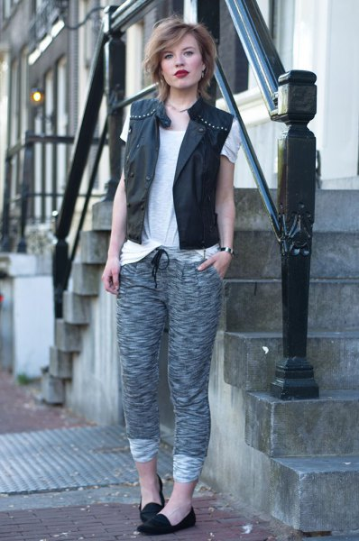 black leather vest with rivets and gray knitted pants