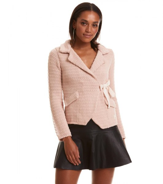 Light pink cardigan with black mini skater leather skirt