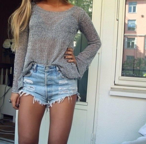 gray, loose-fitting sweater with a scoop neck and light blue jeans shorts in used look