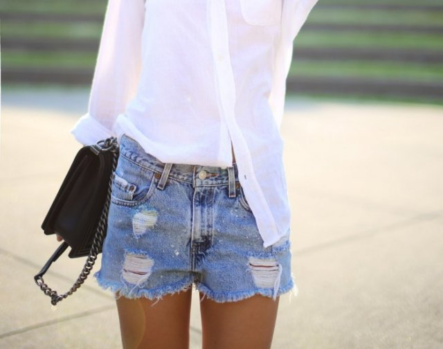 white, slim cut shirt with light blue, high waisted denim shorts in distressed look