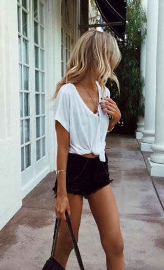 white knotted t-shirt with v-neck and torn black denim shorts