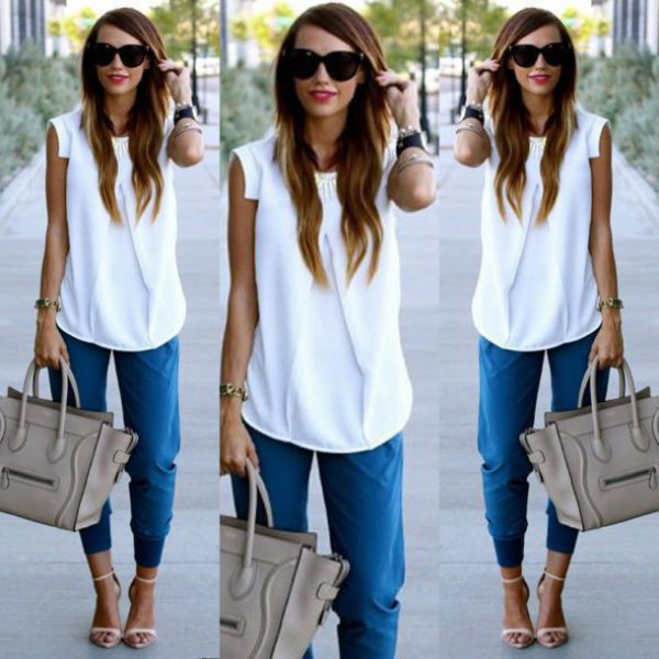 white sleeveless chiffon blouse with blue trousers with a conical leg