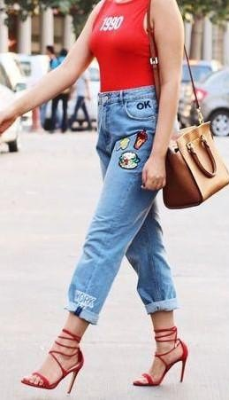 red sleeveless t-shirt with blue embroidered boyfriend jeans