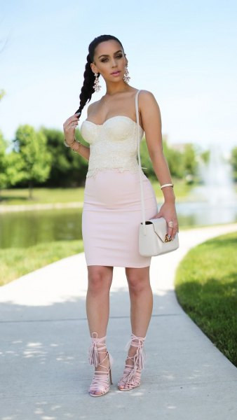 Light pink, form-fitting mini dress with a heart-shaped neckline and white lace-up sandals