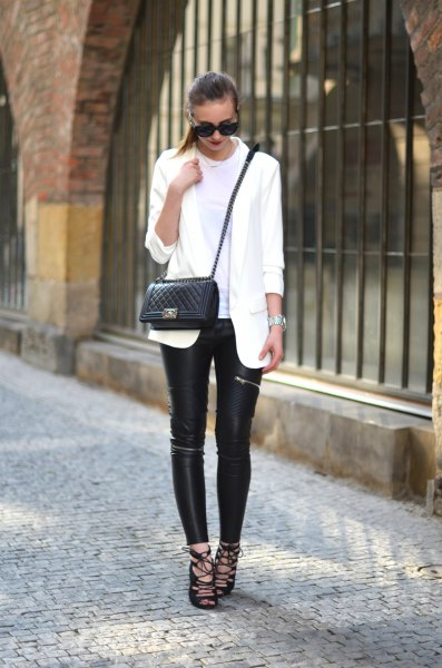 white oversized blazer with black leather leggings and lace-up sandals