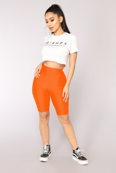 white short graphic t-shirt with long stretch shorts in orange