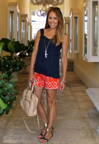 black, loose cut tank top with a heart-shaped neckline and orange shorts with tribal print