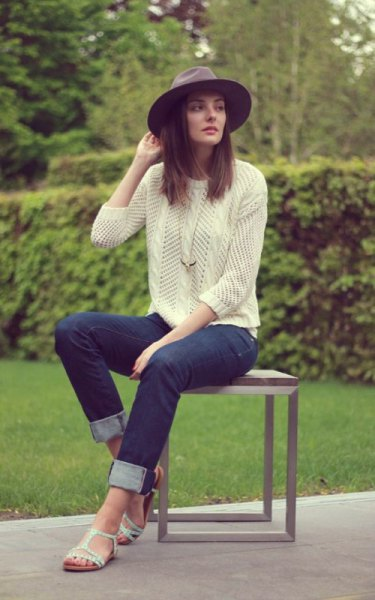Light yellow knit sweater with dark blue slim fit jeans with cuffs and white sandals