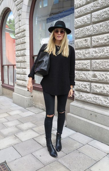 black sweater with heavily torn skinny jeans and boots