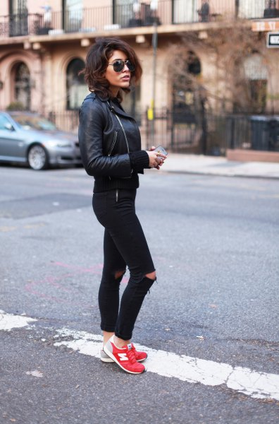 black leather jacket with torn jeans and orange sneakers