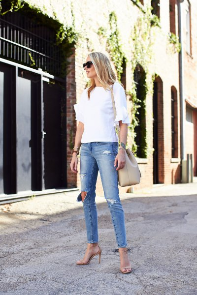 white blouse with frilly sleeves and light blue skinny jeans