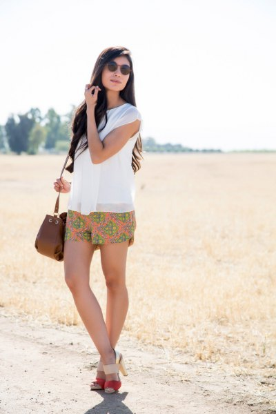 white sleeveless chiffon blouse with orange mini summer shorts with floral pattern