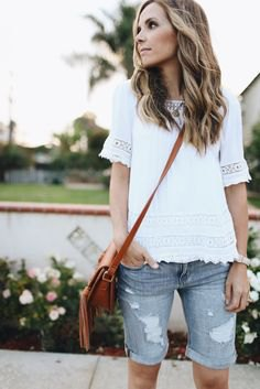 white lace top with torn gray denim shorts