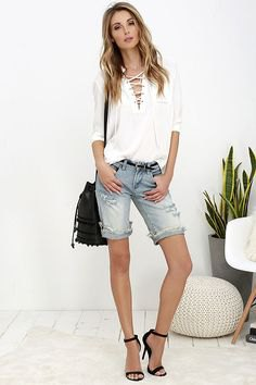 white long-sleeved blouse with cut-out neckline and knee-length denim shorts in light blue
