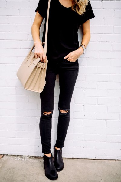 black t-shirt with matching torn skinny jeans and pink purse