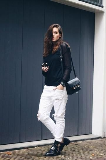 black sweater with stand-up collar and white boyfriend jeans