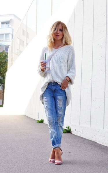 white, coarse-grain knit sweater with blue torn jeans with cuffs