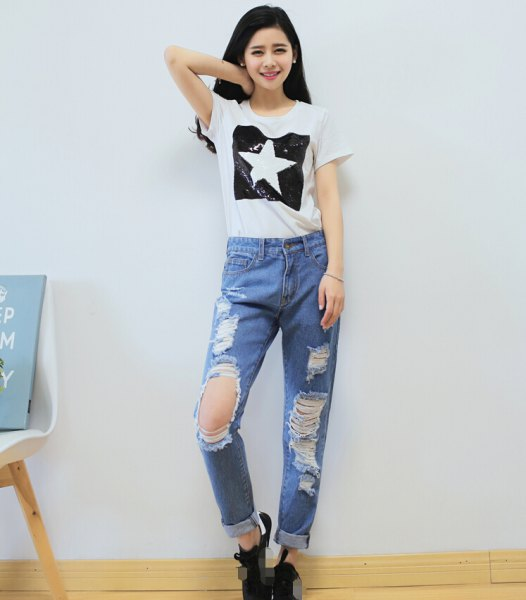 white graphic t-shirt with light blue torn boyfriend jeans