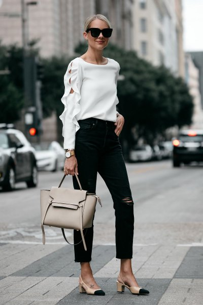 Neckline of white sweater with ankle-black jeans and pink heels