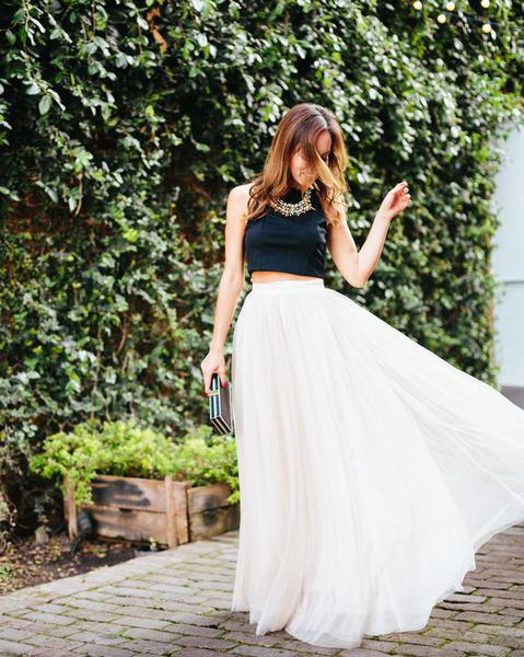 black, short, sleeveless top with white, high waisted maxi pleated skirt