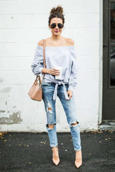 light blue knotted from the shoulder blouse with heavily torn jeans