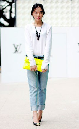 white long-sleeved t-shirt with light blue cuffed jeans and yellow clutch