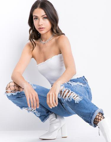 Tube top with heavily torn boyfriend jeans and fishnet stockings