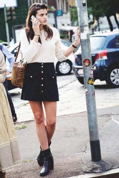 white rib sweater with black mini skirt with button placket and ankle boots