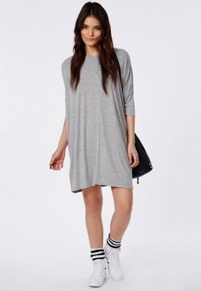 gray t-shirt dress with black leather shoulder bag and white running shoes