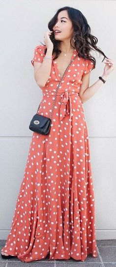 floor-length flared dress in orange and white with polka dots