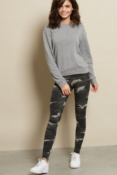 gray, chunky sweater with camouflage leggings and white sneakers